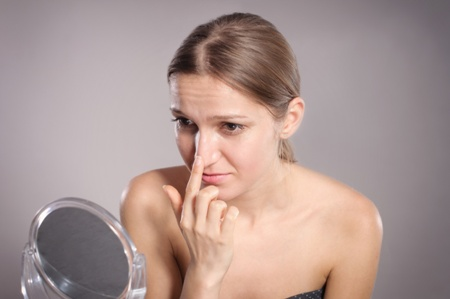 woman looking at the tip of her nose in the mirror