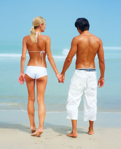 man and woman standing on beach holding hands