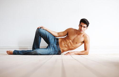 shirtless man propping on his elbow