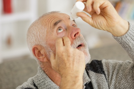 senior man applying eyedrops for glaucoma treatment