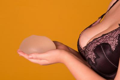 Woman holding a breast implant next to her bra