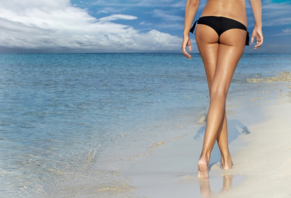 woman with prominent butt walking along the beach