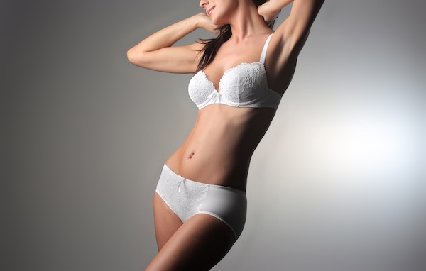 Photo of a thin, shapely woman in a white bra and underwear set after having liposuction