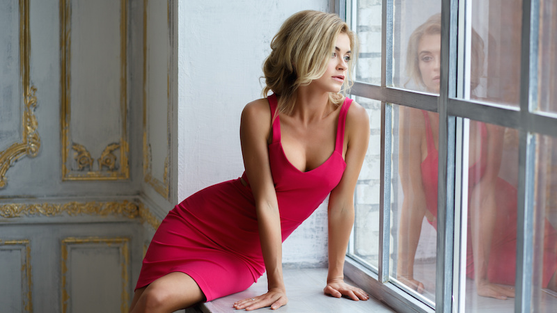 Attractive woman with breast implants wearing a red dress and looking out the window