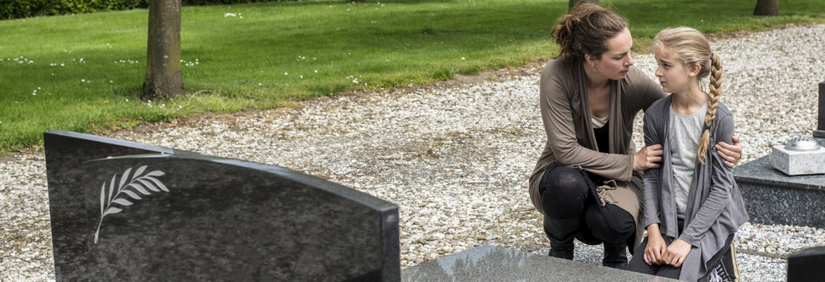 Mother and daughter crying at their loved ones grave