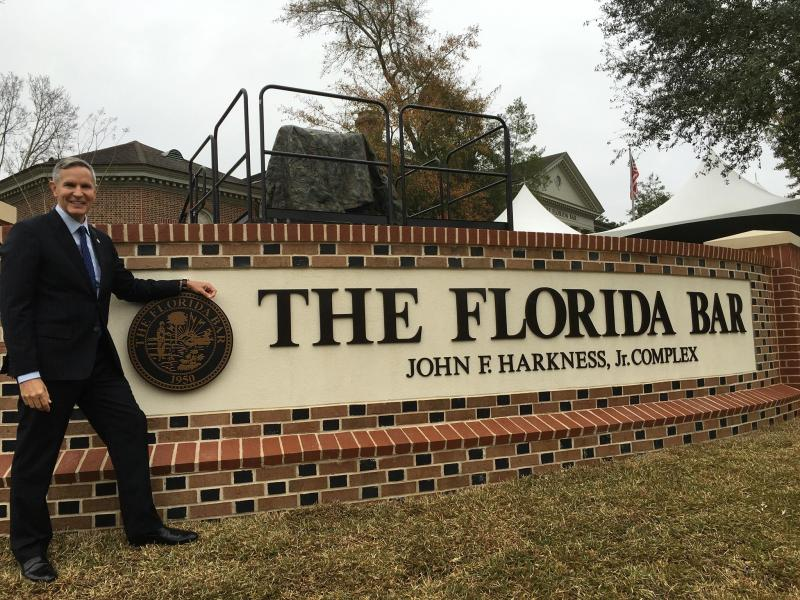 attorney Jack Hickey standing next to The Florida Bar sign