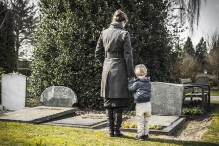 mother and child standing over the grave of a dead loved one