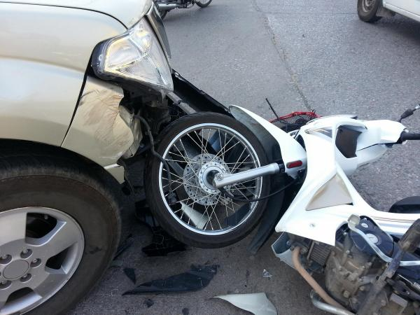 crashed motorcycle lying under front bumper of car after accident