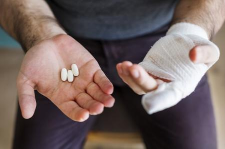 man with bandaged hand holding opioid painkillers in the other hand