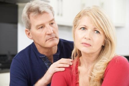 middle-aged man comforting sad middle-aged woman