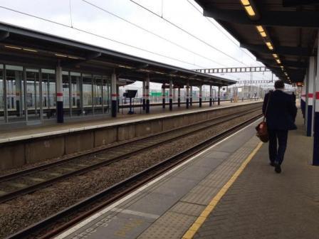 businessman walking on platform next to train tracks