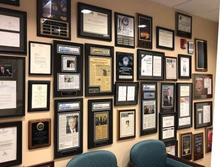 wall of framed awards and certificates for Jack Hickey and the Hickey Law Firm