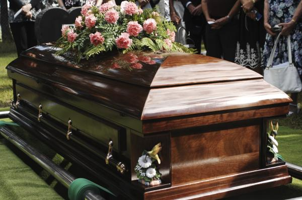 casket at funeral adorned with flowers