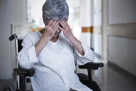 anciana en silla de ruedas sosteniendo su cabeza