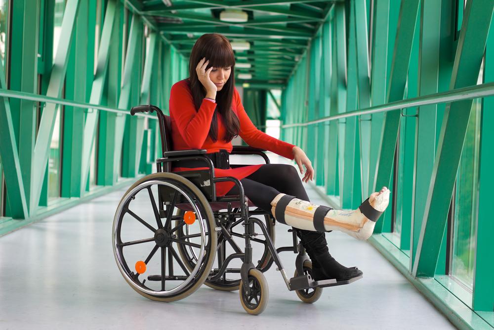 mujer joven triste en silla de ruedas