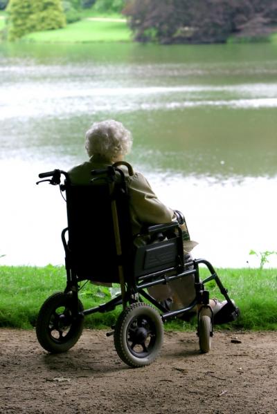 anciana sentada en silla de ruedas junto a un lago