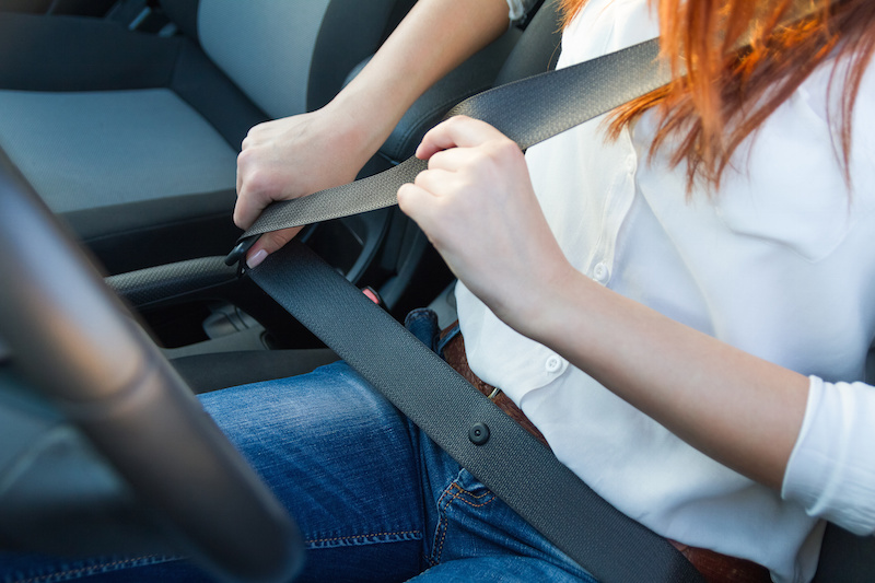 Woman in driver's seat of car in process of fastening seat belt
