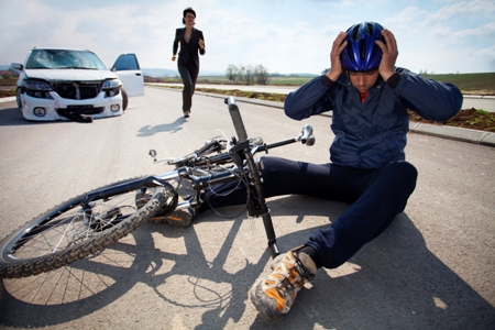 bicyclist clutches head after being hit by car