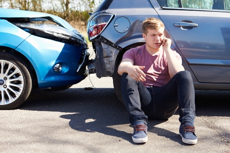 young man on cellphone after rear end car accident
