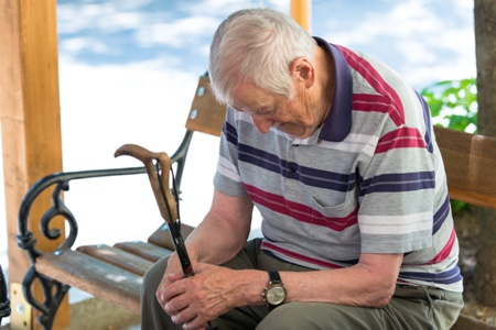sad old man sits on bench clutching his cane