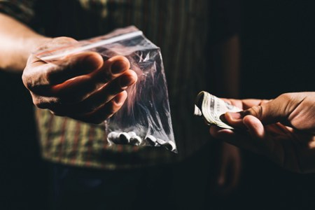 hand exchanging cash for baggy of white pills