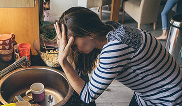 Woman with headache while trying to make dinner for her family