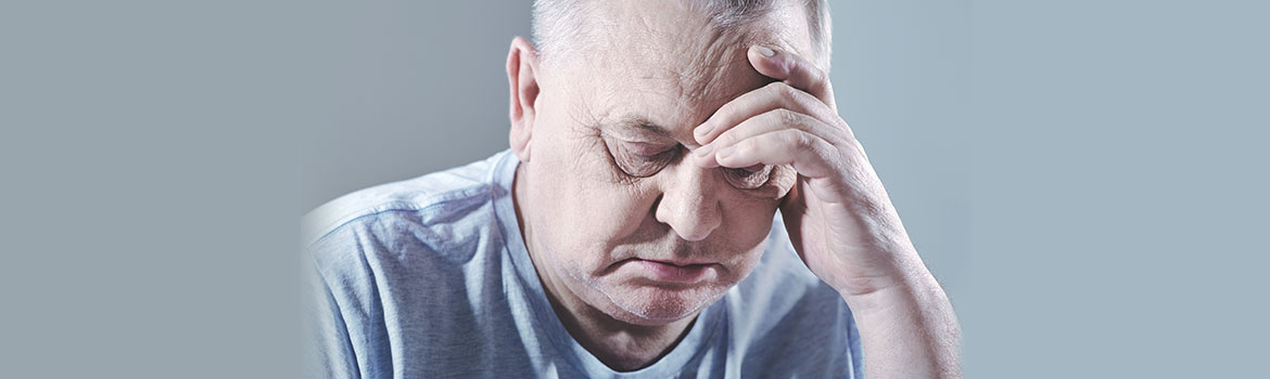Old man with head in hands after a sleepless night from snoring