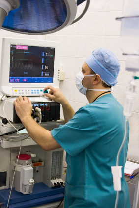 anesthesiologist checks patient monitor