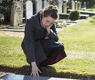 Woman touching a headstone in a cemetery