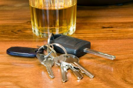 car keys on bar top in front of glass of liquor