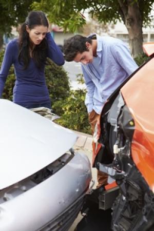 man and woman investigate damage after fender bender