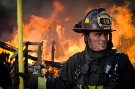 firefighter lieutenant stands in front of burning building