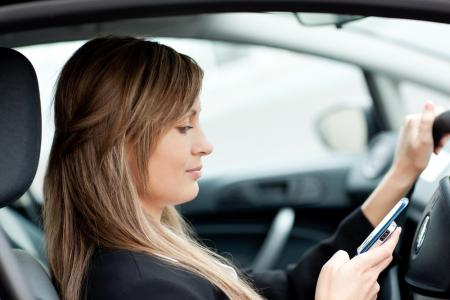 woman in car texting while driving