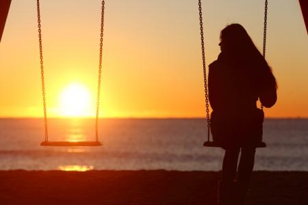 woman on swingset looks at sunset over the ocean