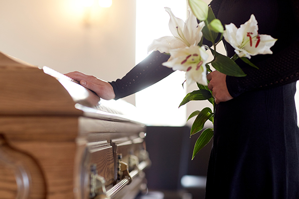Woman holding flowers touches casket at Naples funeral after wrongful death