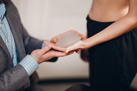 doctor handing breast implant to female patient
