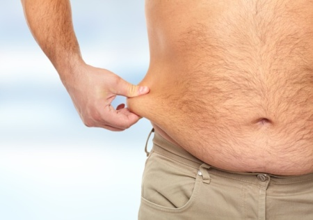 man pinching unwanted fat on his waist