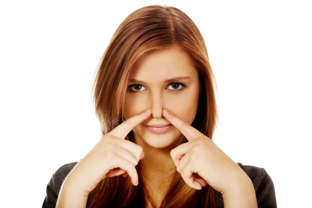 young woman pinching her nose closed with her index fingers