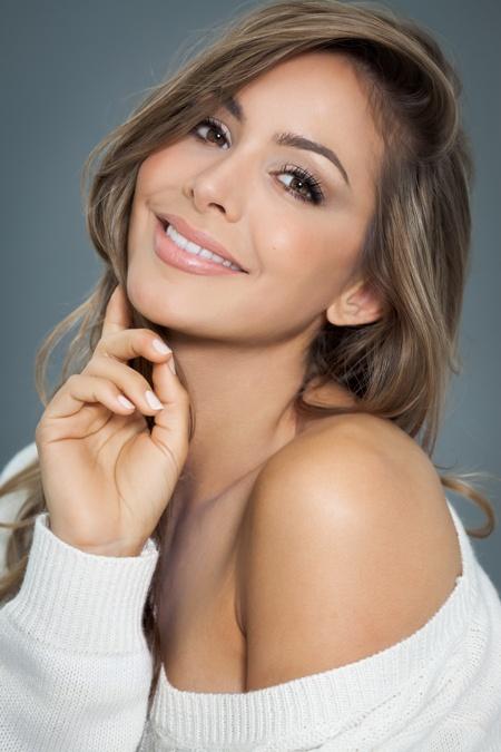 smiling woman resting chin on cheek
