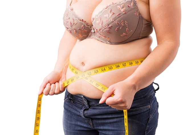 overweight woman measuring her stomach