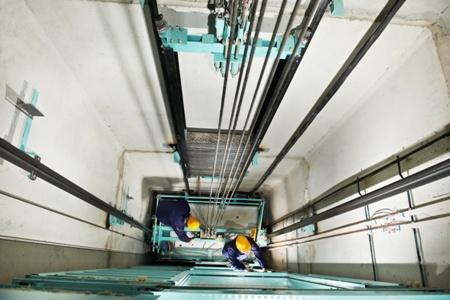 workers repairing broken elevator