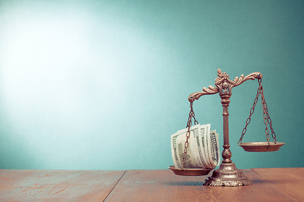 Justice scale balances money to indicate personal injury settlement