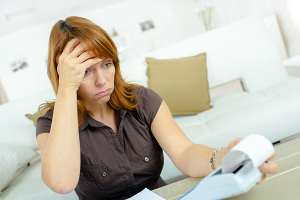 Frustrated woman looks at bills while considering lawsuit loan