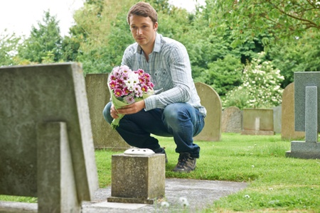 man in cemetery grieving wrongful death of loved one