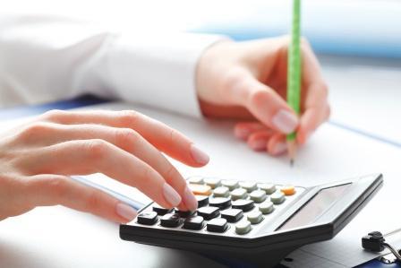 businesswoman's hand typing on desk calculator