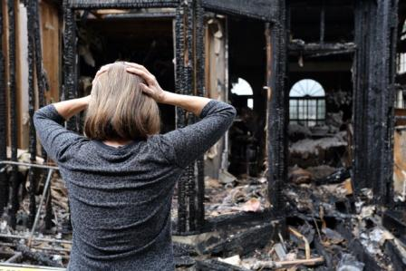 woman holding her head in despair outside of house destroyed by fire