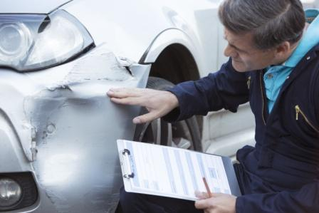 insurance adjuster inspecting car fender after auto accident