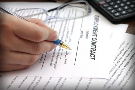 female hand signing an employment contract with a ballpoint pen