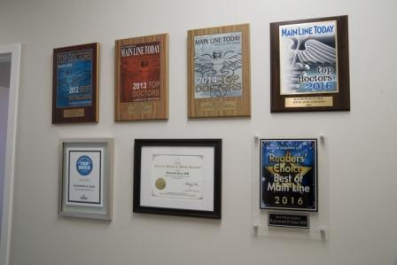 award plaques for Dr. Raymond Jean on the wall at Main Line Plastic Surgery