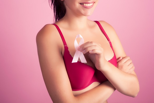 breast cancer patient holding a pink ribbon after breast reconstruction